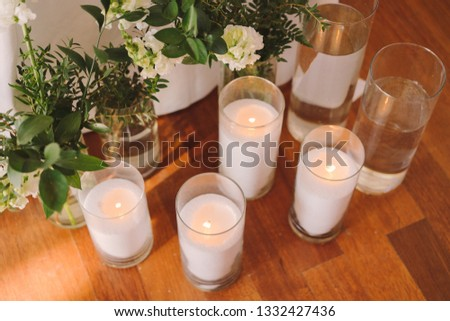Coziness and style. Modern event design. Table setting at wedding reception. Floral compositions with beautiful flowers and greenery, candles, laying and plates on decorated table. #1332427436