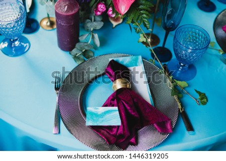 Coziness and style. Modern event design. Table setting at wedding reception. Floral compositions with beautiful flowers and greenery, candles, laying and plates on decorated table. #1446319205