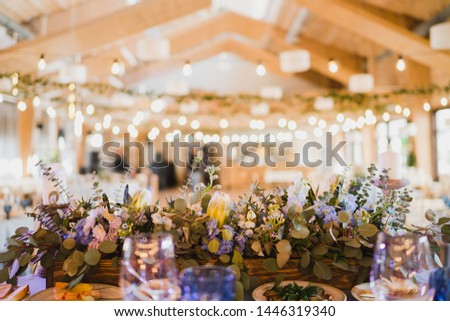 Coziness and style. Modern event design. Table setting at wedding reception. Floral compositions with beautiful flowers and greenery, candles, laying and plates on decorated table. #1446319340