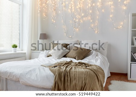 coziness, comfort, interior and holidays concept - cozy bedroom with bed and christmas garland lights at home #519449422