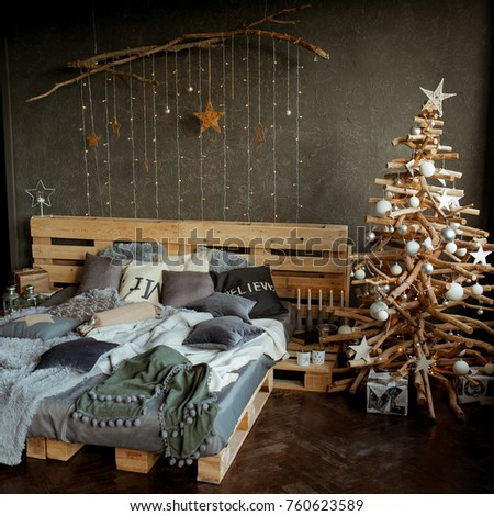 coziness, comfort, interior and holidays concept - cozy bedroom with bed and christmas garland lights at home #760623589