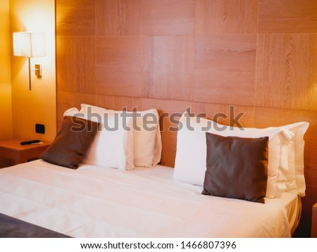 Coziness, comfort, wooden interior and relax concept - cozy bedroom with big comfortable double bed and pillows at home