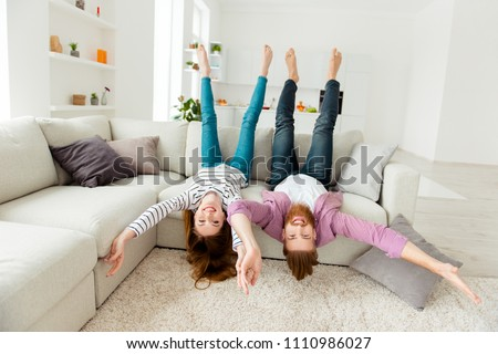 Coziness holiday house friendship funny partners lifestyle leisure concept. Excited cheerful joyful funky rejoicing lovers fooling around lying on divan in living room wearing casual outfit clothes #1110986027
