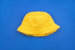Cozy and bright yellow wool plush panama isolated on blue background.