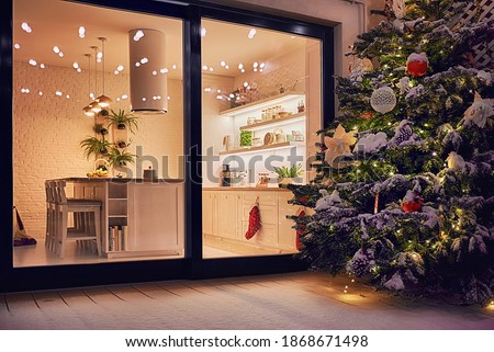 cozy apartment with sliding doors, and decorated christmas tree on the patio at snowy winter night Stockfoto ©