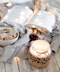 Cozy autumn aesthetic with pumpkin spice cookies, candlelight, a book, glasses, and a comfortable sweater on a wood background