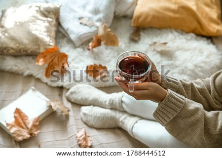 Cozy autumn at home, a woman with tea and a book resting. A cozy way of life . Body parts in the composition.