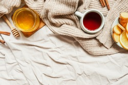 cozy autumn Breakfast with tea, selective focus, honey, cinnamon sticks, lemon, ginger and a warm knitted sweater on a beige mint fabric