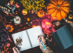 Cozy autumn home lifestyle. Female hand writes in blank notebook on dark desk with  various pumpkins, fall leaves , candles and cappuccino in rustic mug. Top view. Flat lay . Copy space.