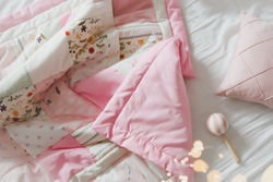 Cozy baby cot with pink patchwork blanket. Baby bedding. Baby crib, close up. Bedding and textile for children nursery. Nap and sleep time.
