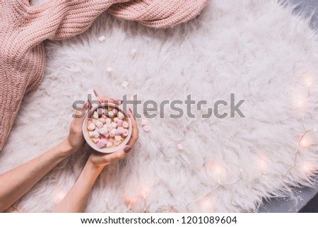Cozy background. Hands holding mug of hot cocoa or hot chocolate with marshmallow on white rug. Copy space #1201089604