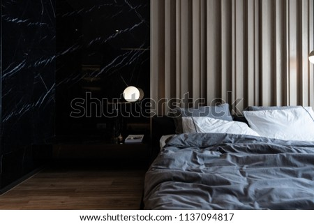 Cozy bedroom corner with nice black marble table lamp in mid century style in front of  wooden strip composition  headboard and natural black marble on the wall #1137094817