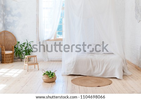 Cozy bedroom in light colors with a wooden floor, a large four-poster bed, wicker chair and basket of flowers. Scandinavian simplicity design. Eco loft apartments.