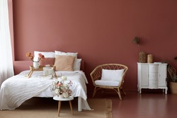 Cozy bedroom interior of retro armchair, vintage chest dwarf and bed on the background of the pink wall and painted wooden floor