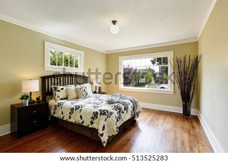 Photo of Cozy bedroom interior. Queen size bed with floral patterned bedding, room decorated with high dry branches in glass vase standing in the corner. Northwest, USA