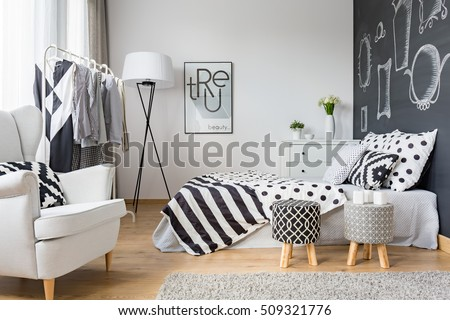 Cozy bedroom with blackboard wall, clothes rack and armchair