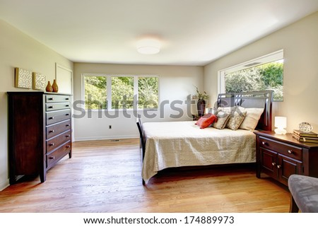 Cozy bedroom with hardwood floor furnished with dark brown wood furniture set and light tones bedding