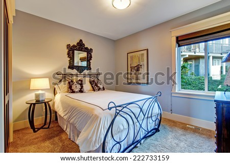 Cozy bedroom with soft brown carpet floor and iron frame bed
