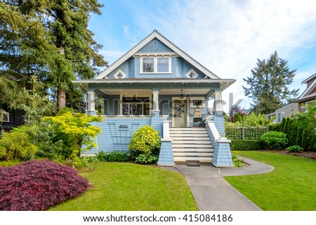 Cozy blue house with a beautiful garden on a sunny day. Home exterior.