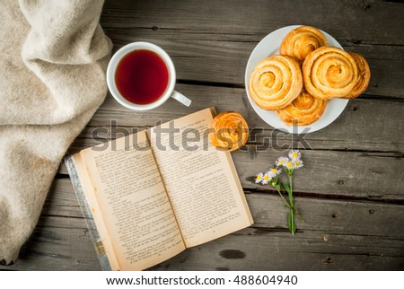 Cozy breakfast in spring or early autumn tea, freshly baked scones and bouquet of field's daisy and fascinating book. Copy space, top view #488604940