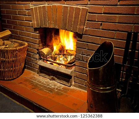 Cozy bright Roaring log fire with brick surround glowing with flames going up chimney