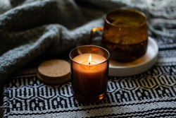 Cozy burning candle in brown glass jar, winter home interior decor with cup and blanket