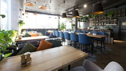 Cozy cafe interior with sofas and tables for quick lunch, angle view, panorama, copy space