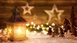 Cozy Christmas arrangement with beautiful wooden ornaments on snow in the warm candlelight of a nice lantern, low-key studio shot