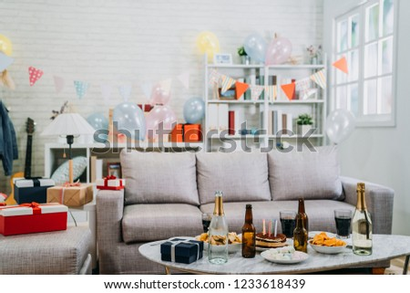cozy decorated bright living room in day time celebrating birthday house party. nobody at home full of food and alcohol drinks on table. colorful balloons and present gifts beside the couch.