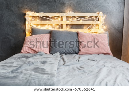 Cozy dreamy bed with decorated DIY pallet headboard #670562641