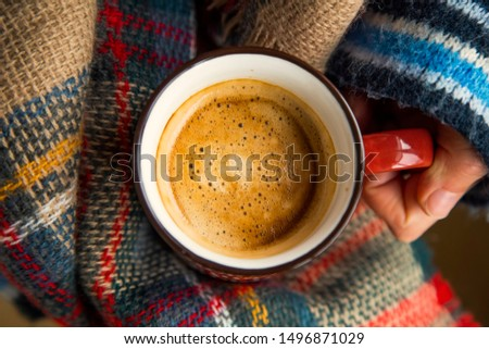 Cozy fall coffee cup top view, woman hands holding warm rustic autumn coffee cup with a cozy blanket, cozy fall still life #1496871029
