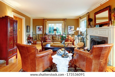 Cozy family room with light tone walls,  old-fashioned furniture, marble table and stoned background fireplace