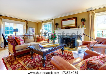 Cozy family room with light tone walls,  old-fashioned furniture, marble table, classic red rug and stoned background fireplace