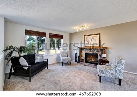 Cozy family room with vintage armchairs and stone trim fireplace. Black sofa and beige carpet. Northwest, USA #467652908