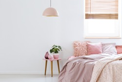 Cozy, feminine bedroom with pink bed, decorative cushions and plant on a wooden stool standing against white, empty wall. Real photo with a place for your furniture.