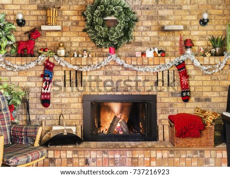 Cozy fire in brick fireplace and mantle decorated for Christmas. Rocking chair, wreath, stockings and basket of blankets part of decor.