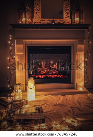 Cozy fireplace with candles blanket and books, Christmas winter home with lights