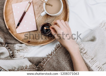 Cozy flatlay with wooden tray, cup of coffee or cocoa, candle, notebooks on white sheets and blankets