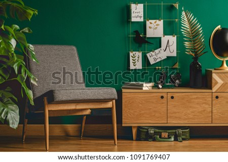 Cozy, green, retro living room interior with chair, cupboard, plant, decorations and wooden floor #1091769407