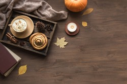 Cozy home and autumn hygge concept. Seasonal autumnal composition with soft plaid, coffee latte, fresh cinnamon bun, candle, pumpkin on wooden, top view, copy space.
