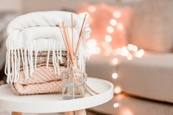 Cozy home decorations in the interior with knitting and aroma diffuser in the living room. Home comfort concept.