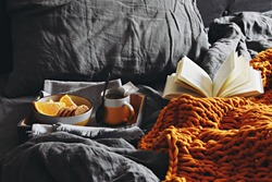 Cozy home with cup of tea with steam, blanket and book. Breakfast in bed.