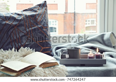 Cozy home with cup of tea with steam, blanket, book and candles. Hygge home interior #747264247