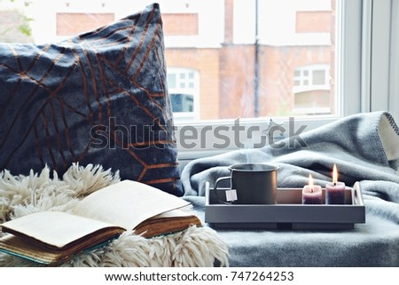 Cozy home with cup of tea with steam, blanket, book and candles. Hygge home interior #747264253