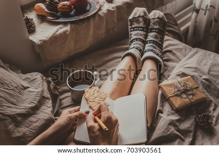 Cozy home. Woman with cup of hot drink sitting by the window and writing in notepad. Selective focus #703903561