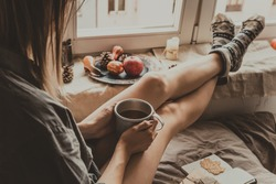 Cozy home. Woman with cup of hot drink sitting by the window. Selective focus