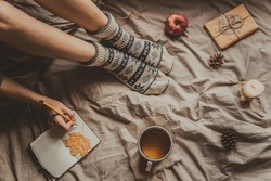 Cozy home. Woman with cup of hot drink writing in notepad. Top view.