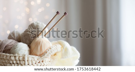 Cozy homely atmosphere. Female hobby knitting. Yarn in warm colors. Pink, peach, beige, white and green. The beginning of the process of knitting a women's sweater. Foto d'archivio ©