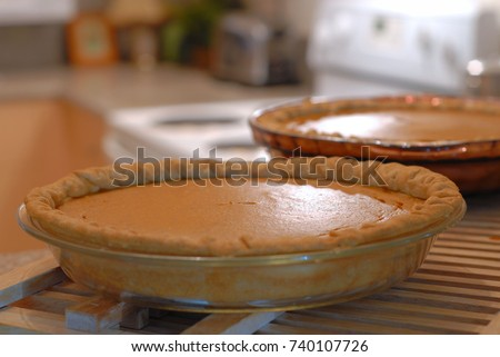 Cozy, homey image of two pumpkin pies cooling in a kitchen. Backlighting and shallow depth of field used. Image is in warm tones to enhance the ambiance.