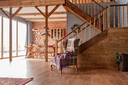 cozy interior of a country house in a wooden design. spacious living room with kitchen area with large windows. bedroom on the second floor.